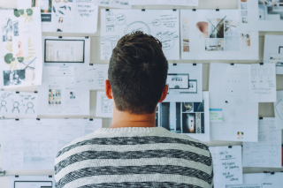 Canva - Man Wearing Black and White Stripe Shirt Looking at White Printer Papers on the Wall