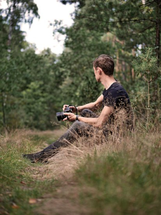 Canva-man-holding-camera-sitting-on-green-grass-MADGvwtJvJY