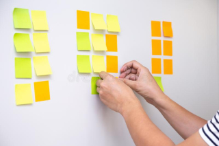 Worker-tracking-his-tasks-kanban-board-using-task-control-agile-development-methodology-man-attaching-sticky-note-to-155290187